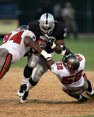 OAKLAND, CA - SEPTEMBER 26:   Running back Tyrone Wheatley #47 of the Oakland Raiders is hit by defensive end Greg Spires #94 and linebacker Marquis Cooper #58 of the Tampa Bay Buccaneers on September 26, 2004 at Network Associates Coliseum in Oakland, Ca