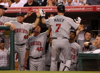ANAHEIM, CA - JULY 24:  Joe Mauer #7 of the Minnesota Twins is greeted after hitting a home run in the fourth inning against the Los Angeles Angels of Anaheim on July 24, 2009 at Angel Stadium in Anaheim, California.  (Photo by Stephen Dunn/Getty Images)