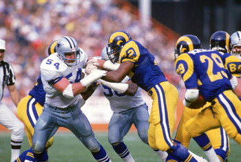 ANAHEIM, CA - JANUARY 4:  Defensive end Randy White #54 of the Dallas Cowboys battles against Kent Hill #72 of the Los Angeles Rams during a 1985 NFC Divisional Playoff game at Anaheim Stadium on January 4, 1996 in Anaheim, California.  The Rams won 20-0.
