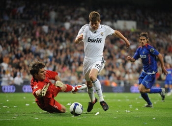 MADRID, SPAIN - APRIL 21: Klaas Jan Huntelaar of Real Madrid tries to get past  Vladimir Stojkovic of Getafe during the La Liga match between Real Madrid and Getafe at the Santiago Bernabeu stadium on April 21,  2009 in Madrid Spain.  (Photo by Denis Doyl