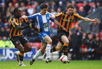 WIGAN, UNITED KINGDOM - MARCH 22:  Paul Scharner (C) of Wigan breaks past Samuel Ricketts (R) and Kamil Zayatte of Hull during the Barclays Premier League match between Wigan Athletic and Hull City at The JJB Stadium on March 22, 2009 in Wigan, England.