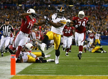 TAMPA, FL - FEBRUARY 01:  James Harrison #92 of the Pittsburgh Steelers scores a touchdown after running back an interception for 100 yards in the second quarter against Larry Fitzgerald #11 of the Arizona Cardinals during Super Bowl XLIII on February 1,