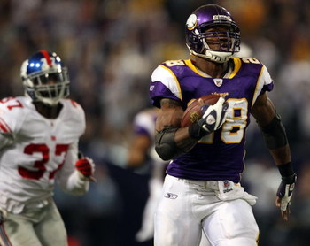 MINNEAPOLIS - DECEMBER 28:  Adrian Peterson #28 of the Minnesota Vikings carries the ball in for a touchdown as James Butler #37 of the New York Giants defends on December 28, 2008 at the Hubert H. Humphrey Metrodome in Minneapolis, Minnesota. (Photo by E