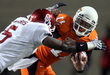 STILLWATER, OK - NOVEMBER 29:  Quarterback Zac Robinson #11 of the Oklahoma State Cowboys runs the ball against Nic Harris #5 of the Oklahoma Sooners at Boone Pickens Stadium on November 29, 2008 in Stillwater, Oklahoma.  (Photo by Ronald Martinez/Getty I