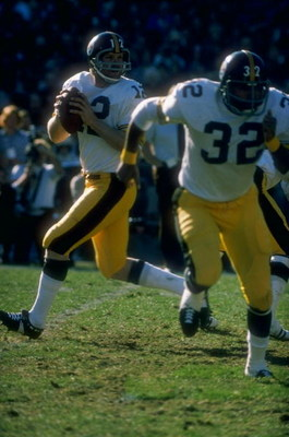 1977:  Quarterback Terry Bradshaw #12 of the Pittsburgh Steelers drops back to pass as teammate Franco Harris #32 runs to get open during a game against the Oakland Raiders at the Oakland Coliseum in Oakland, California. The Raiders defeated the Steelers