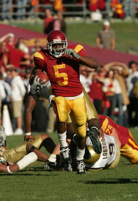 LOS ANGELES, CA - DECEMBER 03:  Reggie Bush #5 of the USC Trojans rushes the ball against the UCLA Bruins December 3, 2005 at the Los Angeles Memorial Coliseum in Los Angeles, California. USC won 66-19.  (Photo by Stephen Dunn/Getty Images)