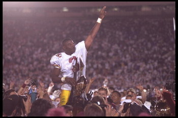 1 Jan 1996:  Wide receiver Keyshawn Johnson of the University of Southern California Trojans raises his arm in triumph in front of the Rose Bowl Trophy after defeating the Northwestern Wildcats in the Rose Bowl in Pasadena, California.  USC defeated North