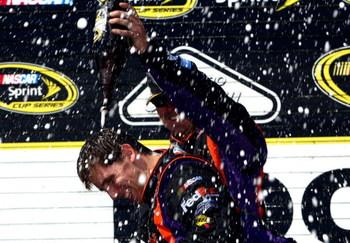 LONG POND, PA - AUGUST 03:  Denny Hamlin (L), driver of the #11 FedEx Express Toyota, celebrates with a crew member in victory lane after winning the NASCAR Sprint Cup Series Sunoco Red Cross Pennsylvania 500 at the Pocono Raceway on August 3, 2009 in Lon