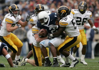 STATE COLLEGE, PA - OCTOBER 23:  Quarterback Michael Robinson #12 of the Penn State Nittnay Lions is tackled by George Lewis #50 and the Iowa Hawkeyes defense as Iowa defeated Penn State 6-4 during NCAA football at Beaver Stadium on October 23, 2004 in St
