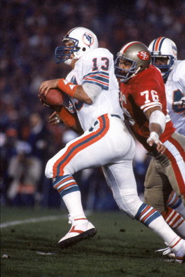 STANFORD, CA - JANUARY 20:  Quarterback Dan Marino #20 of the Miami Dolphins gets sacked by defensive end Dwaine Board #76 of the San Francisco 49ers during Super Bowl XIX at Stanford Stadium on January 20, 1985 in Stanford, California.   The 49ers won 38