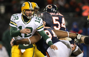 CHICAGO - DECEMBER 22: Marcus Harrison #94 of the Chicago Bears hits Aaron Rodgers #12 of the Green Bay Packers after he passes on December 22, 2008 at Soldier Field in Chicago, Illinois. The Bears defeated the Packers 20-17 in overtime. (Photo by Jonatha