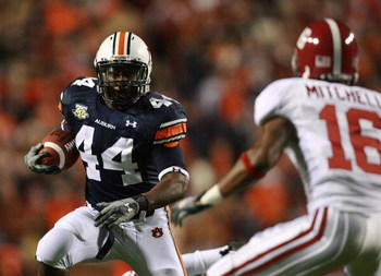 AUBURN, AL - NOVEMBER 24:  Running back Ben Tate #44 of the Auburn Tigers looks to avoid a tackle by defensive back Lionel Mitchell #16 of the Alabama Crimson Tide at Jordan-Hare Stadium on November 24, 2007 in Auburn, Alabama.  (Photo by Doug Benc/Getty