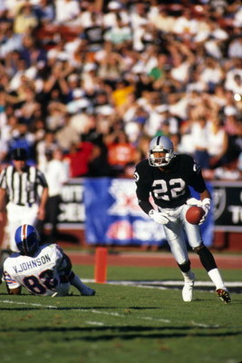 LOS ANGELES - DECEMBER 4:  Defensive back Mike Haynes #22 of the Los Angeles Raiders looks for room to run against the Denver Broncos wide receiver Vance Johnson #82 during a game at the Los Angeles Memorial Coliseum on December 4, 1988 in Los Angeles, Ca