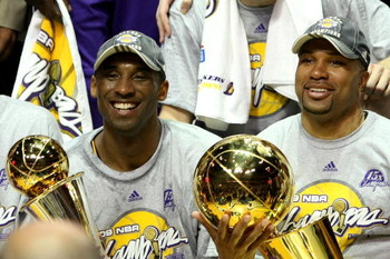 ORLANDO, FL - JUNE 14:  Kobe Bryant #24 of the Los Angeles Lakers holds the Bill Russell MVP trophy and Derek Fisher #2 of the Lakers holds the Larry O'Brien trophy after the Lakers defeated the Orlando Magic 99-86 in Game Five of the 2009 NBA Finals on J