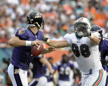 MIAMI, FL - JANUARY 4:  Linebacker Matt Roth #98 of the Miami Dolphins rushes quarterback Joe Flacco #5 of the Baltimore Ravens in an NFL Wildcard Playoff Game at Dolphins Stadium on January 4, 2009 in Miami, Florida.  (Photo by Al Messerschmidt/Getty Ima