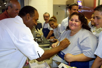 393685 05: O.J. Simpson signs a fans shirt during a visit to the hip-hop concert the 'The First Damn Birthday Jam' August 24, 2001 at TECO arena in Estero, Florida. (Photo by Joe Raedle/Getty Images)