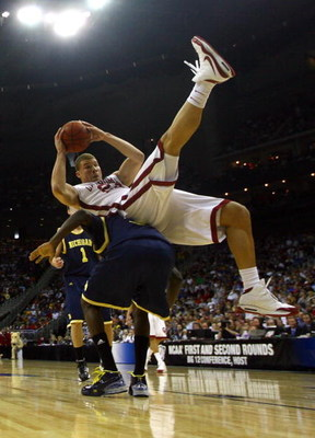 KANSAS CITY, MO - MARCH 21:  Blake Griffin #23 of the Oklahoma Sooners falls on the back of Manny Harris #3 of the Michigan Wolverines during the second round of the NCAA Division I Men's Basketball Tournament at the Sprint Center on March 21, 2009 in Kan