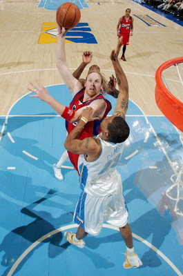 DENVER - APRIL 29:  Chris Kaman #35 of the Los Angeles Clippers shoots over Marcus Camby #23 of the Denver Nuggets in game four of the Western Conference Quarterfinals during the 2006 NBA Playoffs on April 29, 2006 at the Pepsi Center in Denver, Colorado.