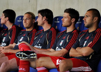 BARCELONA, SPAIN - AUGUST 02:  Xabi Alonso (2nd R) of Liverpool sits on the bench with his teammates prior to the pre-season friendly match between Espanyol and Liverpool at the Nuevo Estadio de Cornella-El Prat on August 2, 2009 in Barcelona, Spain.  (Ph