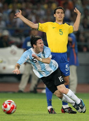 BEIJING - AUGUST 19:  Lionel Messi of Argentina goes down after a challenge from Hernanes of Brazil during the men's football semifinal match at Workers' Stadium on Day 11 of the Beijing 2008 Olympic Games on August 19, 2008 in Beijing, China.  (Photo by