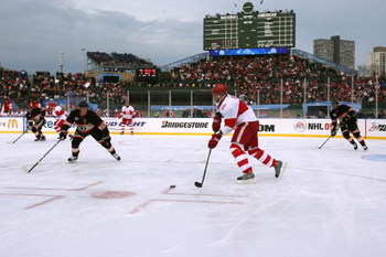 CHICAGO - JANUARY 01:  Andreas Lilja #3 of the Detroit Red Wings moves the puck against    Jonathan Toews #19 of the Chicago Blackhawks during the NHL Winter Classic at Wrigley Field on January 1, 2009 in Chicago, Illinois.  (Photo by Jonathan Daniel/Gett
