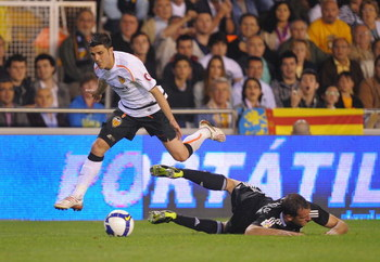 VALENCIA, SPAIN - MAY 09:  David Villa (L) of Valencia leaps over a beaten Cristoph Metzelder of Real Madrid during the La Liga match between Valencia and Real Madrid at the Mestalla stadium on May 9, 2009 in Valencia, Spain.  (Photo by Denis Doyle/Getty