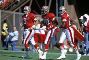 SAN FRANCISCO - SEPTEMBER 24:  (L-R) Quarterback Steve Young #8, wide receivers Jerry Rice #80 and Nate Singleton #88 of the San Francisco 49ers run on the field during a game against the New Orleans Saints at Candlestick Park on September 24, 1994 in San