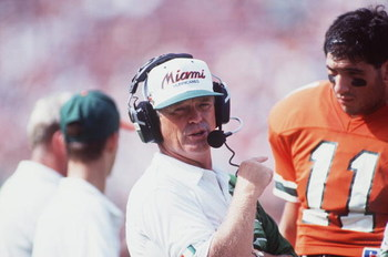 30 OCT 1993:  UNIVERSITY OF MIAMI HEAD COACH DENNIS ERICKSON TALKS WITH AN ASSISTANT COACH AS QUARTERBACK FRANK COSTA #11 STANDS NEARBY AND LISTENS IN DURING THE HURRICANES 42-7 WIN OVER THE TEMPLE UNIVERSITY OWLS AT THE ORANGE BOWL IN MIAMI, FLORIDA. Man