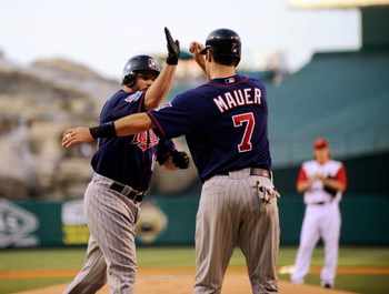 ANAHEIM, CA - JULY 23:  Jason Kubel #16 of the Minnesotta Twins is congratulated by teammate Joe Maur #7 after hitting a two-run home run off pitcher Jered Weaver #36 of the Los Angeles Angels of Anaheim during the first inning of the baseball game on Jul