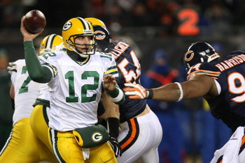 CHICAGO - DECEMBER 22: Aaron Rodgers #12 of the Green Bay Packers looks for a receiver under pressure from Marcus Harrison #94 of the Chicago Bears on December 22, 2008 at Soldier Field in Chicago, Illinois. The Bears defeated the Packers 20-17 in overtim