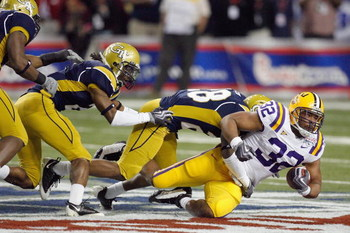 ATLANTA - DECEMBER 31:  Charles Scott #32 of the LSU Tigers is tackled by Rashaad Reid #28 of the Georgia Tech Yellow Jackets  during the Chick-fil-A Bowl on December 31, 2008 at the Georgia Dome in Atlanta, Georgia. (Photo by Kevin C. Cox/Getty Images)
