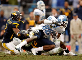 CHARLOTTE, NC - DECEMBER 27:  Hakeem Nicks #88 of the North Carolina Tar Heels is tackled by Franchot Allen #20 of the West Virginia Mountaineers during the Meineke Car Care Bowl on December 27, 2008 at Bank of America Stadium in Charlotte, North Carolina