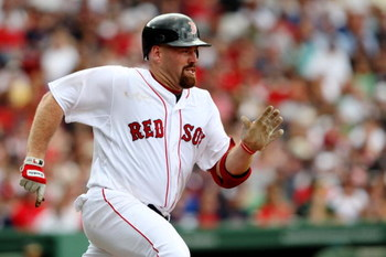 BOSTON - JULY 30:  First baseman Kevin Youkilis #12 of the Boston Red Sox singles against the Oakland A's in the third inning on July 30, 2009 at Fenway Park in Boston, Massachusetts.  (Photo by Elsa/Getty Images)