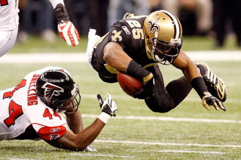 NEW ORLEANS - DECEMBER 07:  Reggie Bush #25 of the New Orleans Saints is tripped by Jason Snelling #44 of the Atlanta Falcons on December 7, 2008 at the Superdome in New Orleans, Louisiana.  (Photo by Chris Graythen/Getty Images)