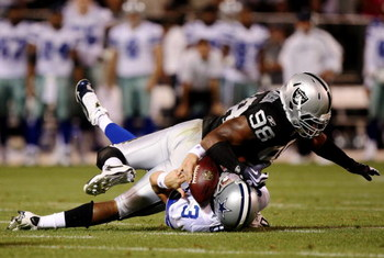 OAKLAND, CA - AUGUST 13:  Defensive end Jay Richardson #98 of the Oakland Raiders sacks quarterback Jon Kitna #3 of the Dallas Cowboys after a bad snap during the preseason game at Oakland-Alameda County Coliseum on August 13, 2009 in Oakland, California.