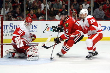 CHICAGO - MAY 24:  Goalie Chris Osgood #30 of the Detroit Red Wings makes a save on a shot attempt by Jonathan Toews #19 of the Chicago Blackhawks as Brian Rafalski #28 of the Red WIngs trails on the play during the first period of Game Four of the Wester