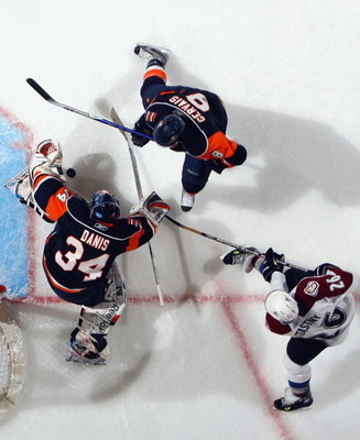 UNIONDALE, NY - MARCH 02:  Paul Stastny #26 of the Colorado Avalanche battles for the puck against Bruno Gervais #8 and Yann Danis #34 of the New York Islanders on March 2, 2009 at Nassau Coliseum in Uniondale, New York. The Isles defeated the Avalanche 4