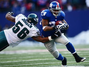 EAST RUTHERFORD, NJ - JANUARY 11:  Derrick Ward #34 of the New York Giants runs against Akeem Jordan #56 of the Philadelphia Eagles during the NFC Divisional Playoff Game on January 11, 2009 at Giants Stadium in East Rutherford, New Jersey.  (Photo by Chr