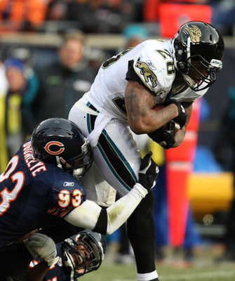 CHICAGO - DECEMBER 07: Fred Taylor #28 of the Jacksonville Jaguars tries to break away from Adewale Ogunleye #93 and Israel Idonije #71 of the Chicago Bears on December 7, 2008 at Soldier Field in Chicago, Illinois. The Bears defeated the Jaguars 23-10. (