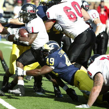 ANN ARBOR - SEPTEMBER 3:  John Thompson #49 of Michigan tackles Garrett Wolfe #1 of Northern Illinois at Michigan Stadium on September 3, 2005 in Ann Arbor, Michigan.  Michigan won the game, 33-17. (Photo by Tom Pidgeon/Getty Images)