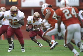 12 Oct 1996: Running back Warrick Dunn #28 of the Florida State Seminoles keeps his eyes focused upfield at pursuing defenders from the Miami Hurricanes as he makes a cut through a hole in the offensive line during a carry in the Seminoles 34-16 victory o