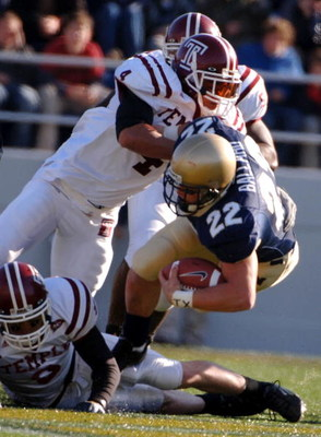 ANNAPOLIS, MD - NOVEMBER 19:  In this handout from the U.S. Navy, U.S. Naval Academy Midshipman full back Adam Ballard #22 is tackled by Temple Owls defender Justin Johnson #4 during the 1st quarter of play on November 19, 2005 at Navy Memorial Stadium in