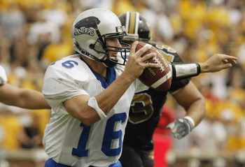 COLUMBIA, MO - SEPTEMBER 13:  Quarterback Andy Vincent #16 of Eastern Illinois scrambles as he is chased by Russ Bell #73 of Missouri on September 13, 2003 at Memorial Stadium in Columbia, Missouri.  Missouri defeated Eastern Illinois 37-0.  (Photo by Els
