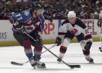 31 May 2001:  Ray Bourque #77 of the Colorado Avalanche passes the puck as John Madden #11 of the New Jersey Devils defends during game three of the NHL Stanley Cup Finals at Continental Airlines Arena in East Rutherford, New Jersey.  DIGITAL IMAGE Mandat