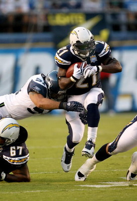 SAN DIEGO - AUGUST 15:    Running back LaDainian Tomlinson #21 of  the San Diego Chargers carries the ball as linebacker David Hawthorne #57 of the Seattle Seahawks defends on August 15, 2009 at Qualcomm Stadium in San Diego, California.    (Photo by Step