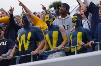 MORGANTOWN, WV - OCTOBER 26:  Fans of the West Virginia University Mountaineers cheer on their team during a Big East game against the University of Miami Hurricanes on October 26, 2002 at Mountaineer Field in Morgantown, West Virginia . Miami won 40-23.