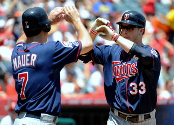 ANAHEIM, CA - JULY 26:  Justin Morneau #33 of the Minnesota Twins celebrates his two-run home run with teammate Joe Mauer #7 during the first inning against the Los Angeles Angels of Anaheim at Angels Stadium on July 26, 2009 in Anaheim, California. (Phot