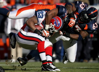 DENVER - DECEMBER 21:  Running back Marshawn Lynch #23 of the Buffalo Bills is tackled by Jamie Winborn #51 and Dewayne Robertson #63 of the Denver Broncos during NFL action at Invesco Field at Mile High on December 21, 2008 in Denver, Colorado. The Bills