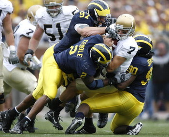 ANN ARBOR, MI - SEPTEMBER 15: Jimmy Clausen #7 of the Notre Dame Fighting Irish is sacked by Shawn Crable #2, Tim Jamison #90 and Will Johnson #97 of the  Michigan Wolverines at Michigan Stadium September 15, 2007 in Ann Arbor, Michigan. (Photo By Gregory