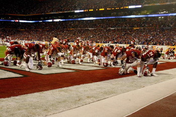 MIAMI - JANUARY 08:  Players from the Oklahoma Sooners kneel and pray in the endzone prior to playing against the Florida Gators during the FedEx BCS National Championship game at Dolphin Stadium on January 8, 2009 in Miami, Florida.  (Photo by Doug Benc/